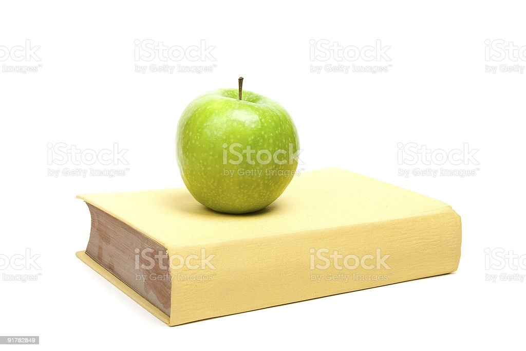 Book and green apple. White background royalty-free stock photo