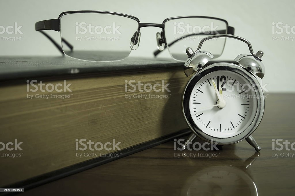 Book, clock and glasses stock photo