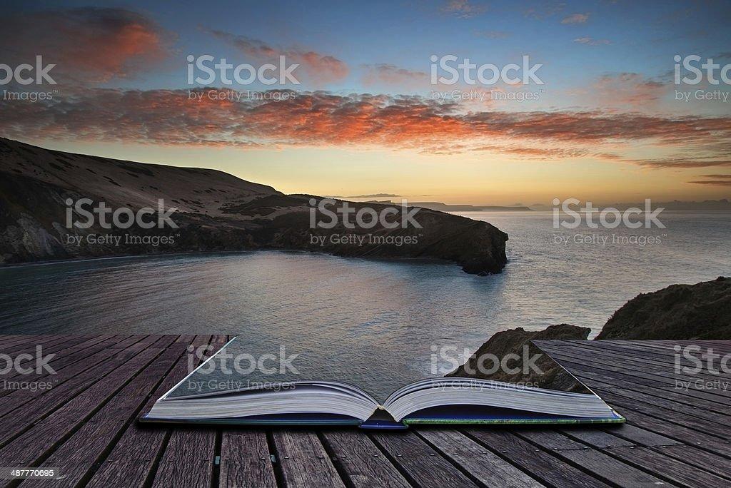Book concept Beautiful vibrant sunrise over rocky coastline stock photo