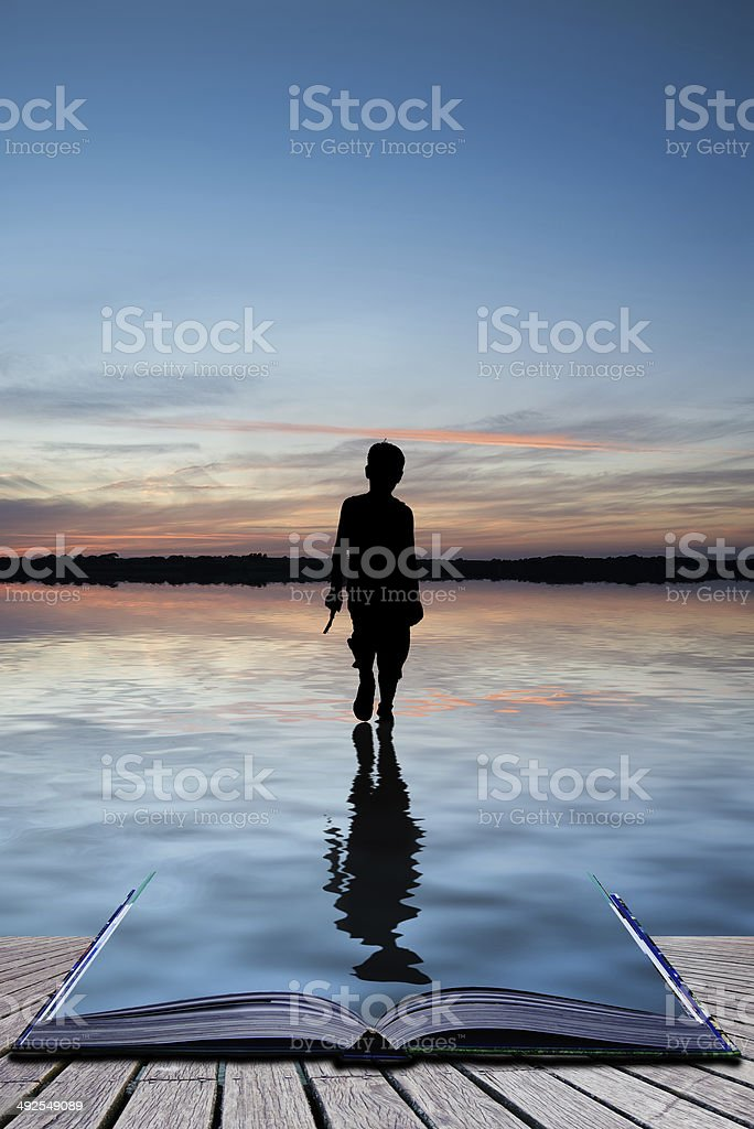 Book concept Concept image of young boy walking on water stock photo