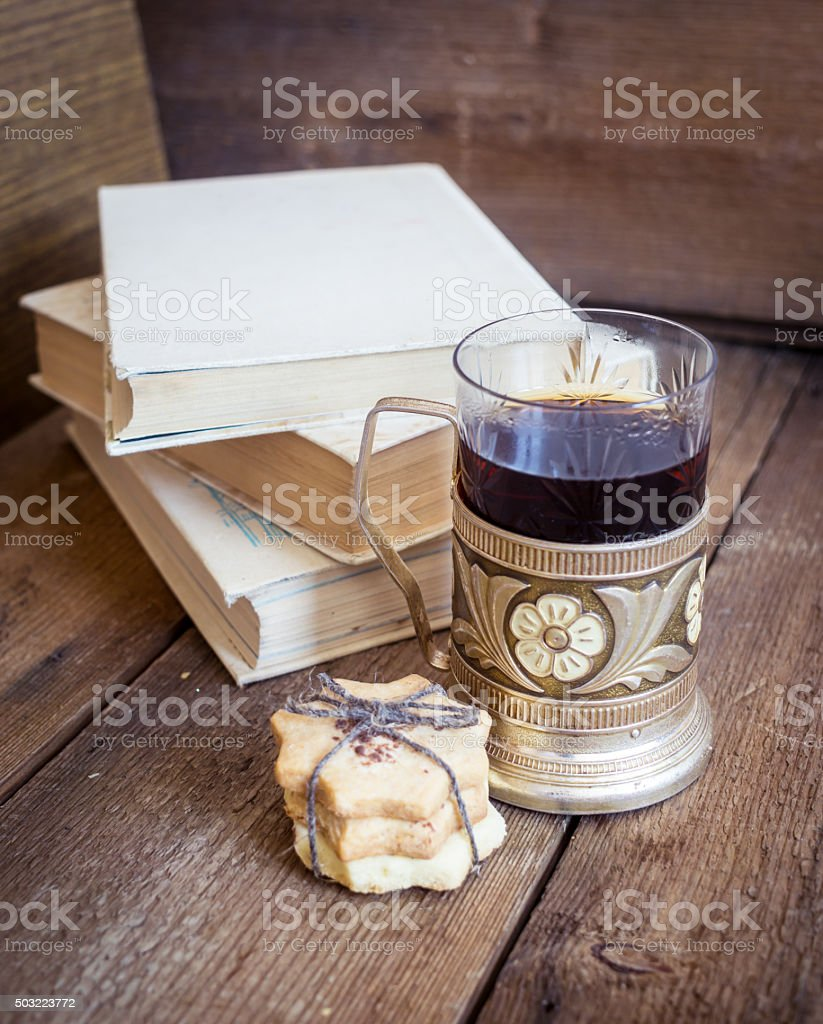 Book, cookies and tea in coaster on wooden background stock photo