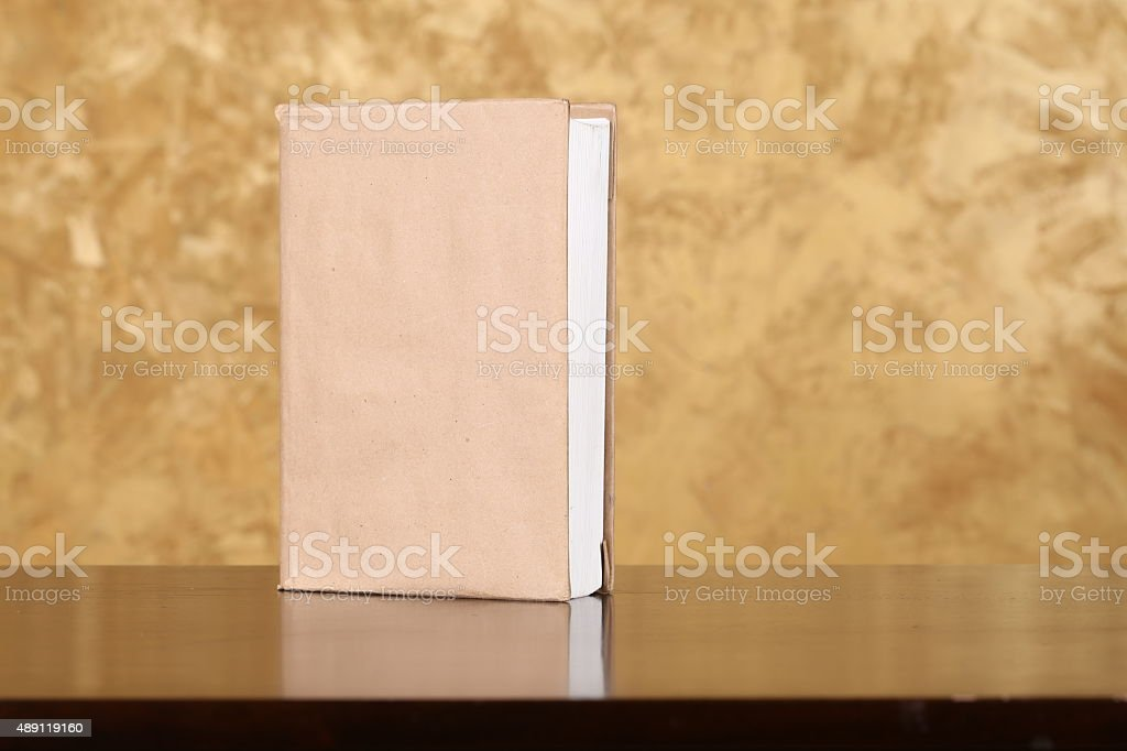Book is on the wooden table and brown background stock photo