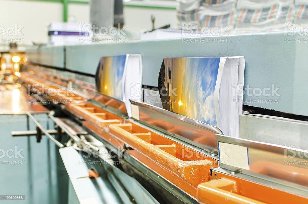 Book, magazine, catalog production line into press plant house. stock photo