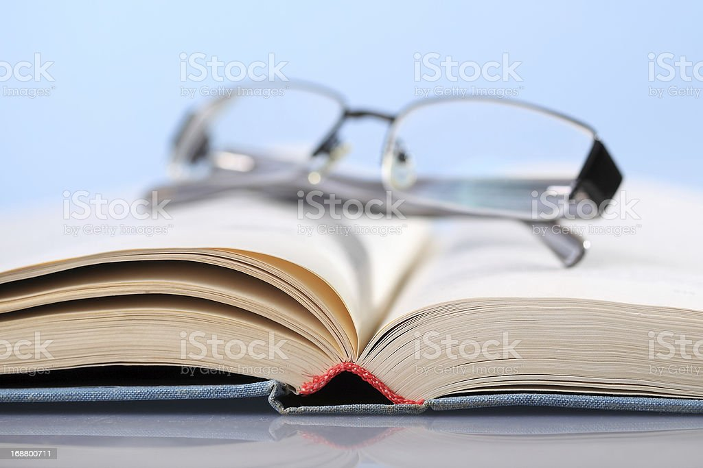 Book on blue with eyeglasses royalty-free stock photo