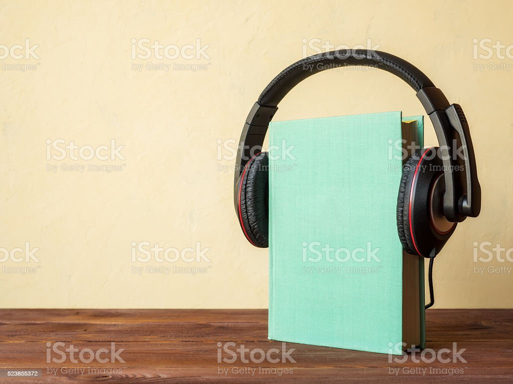 Book on the table with headphones stock photo