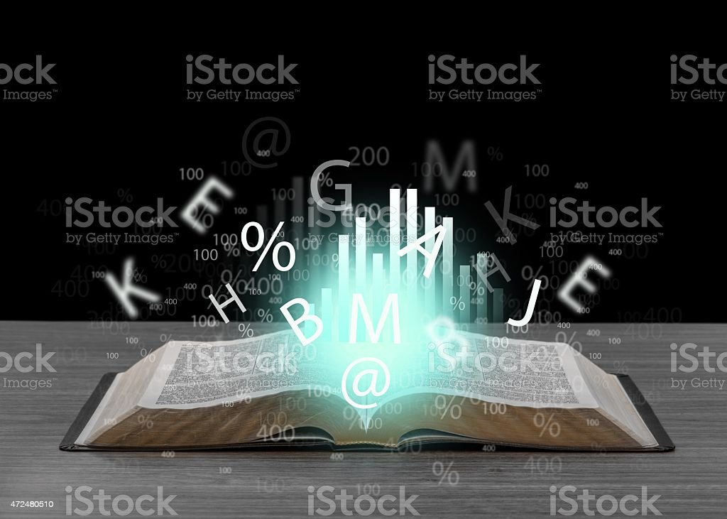 Book on wooden deck with glowing graph illustrations and symbols stock photo