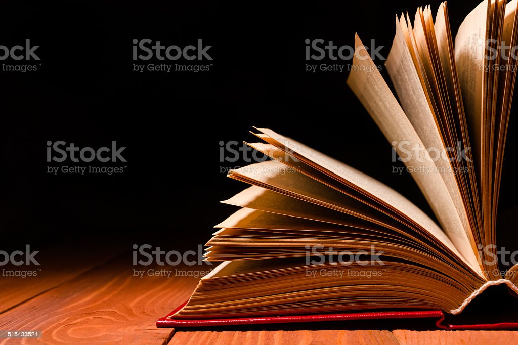 Book opened in library on wooden shelf. Education background with stock photo