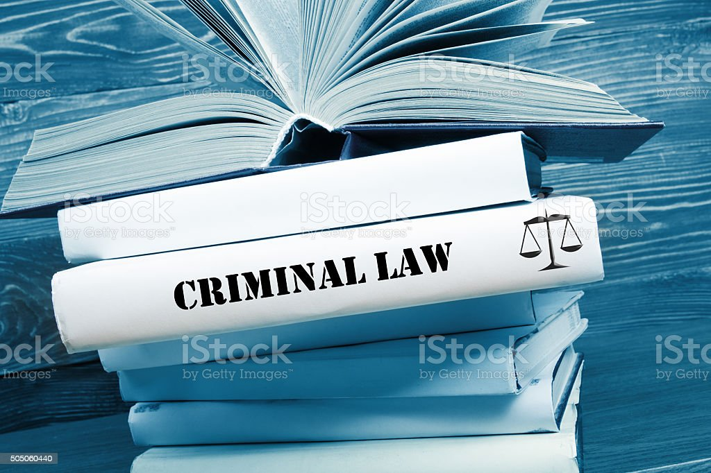 Book with Criminal Law word on table in a courtroom stock photo