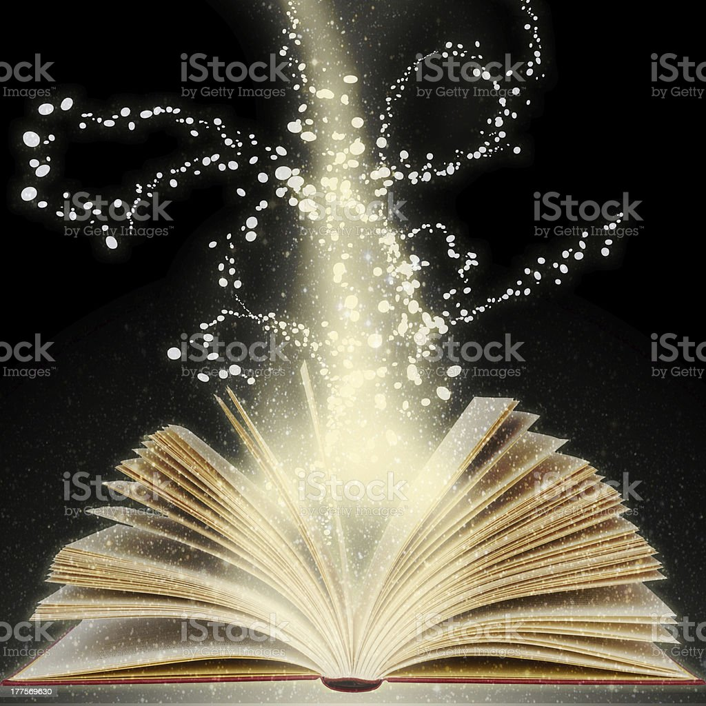 Book with light beams coming from its open pages stock photo