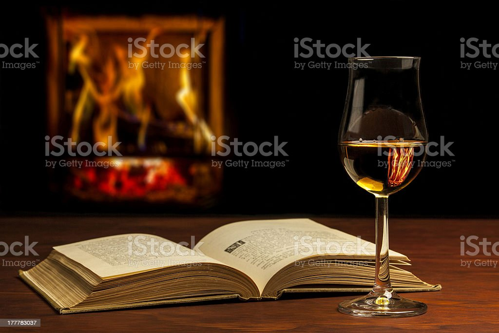 Book with Whisky in front of a fireplace. stock photo
