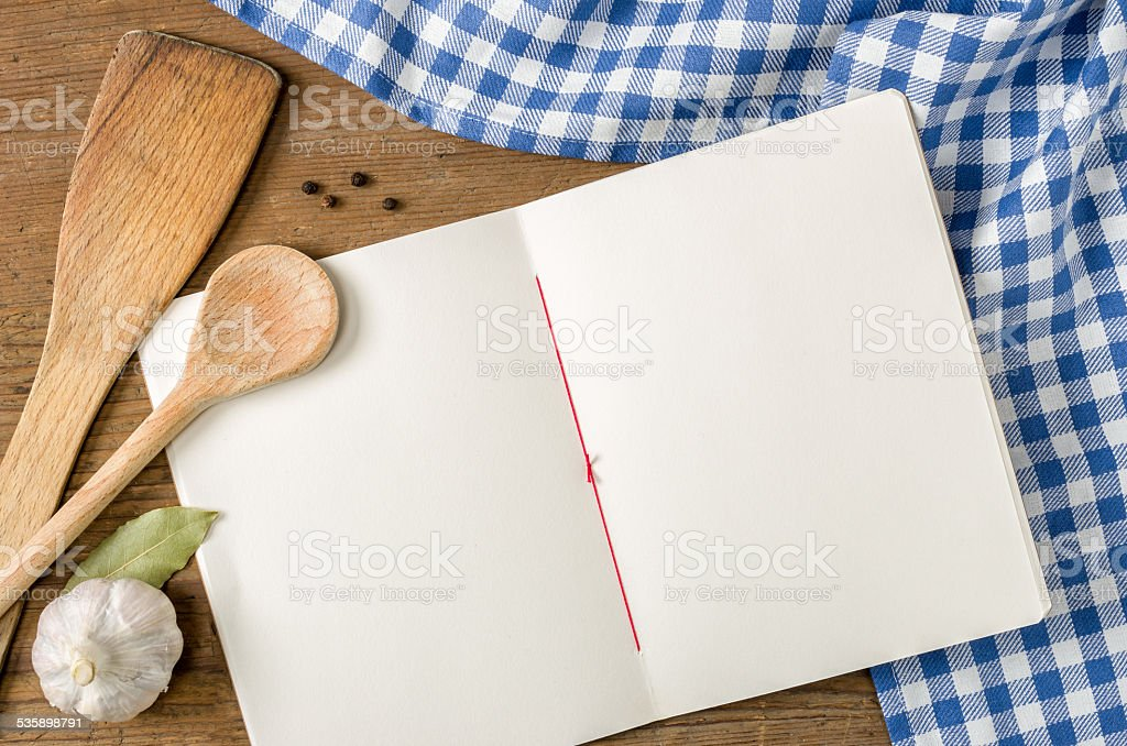 Book with wooden spoons on a blue checkered tablecloth stock photo