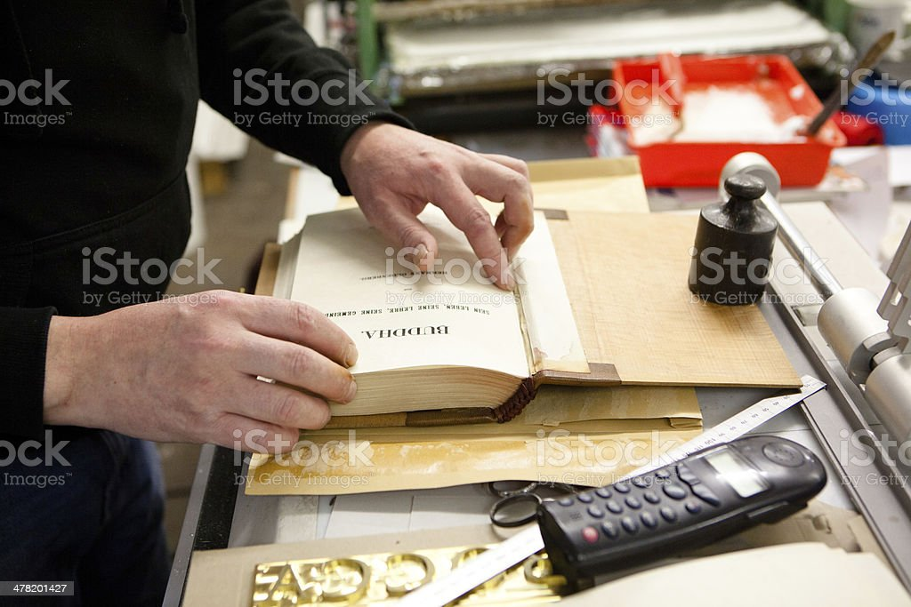 bookbinder in his workshop restores an antique book royalty-free stock photo