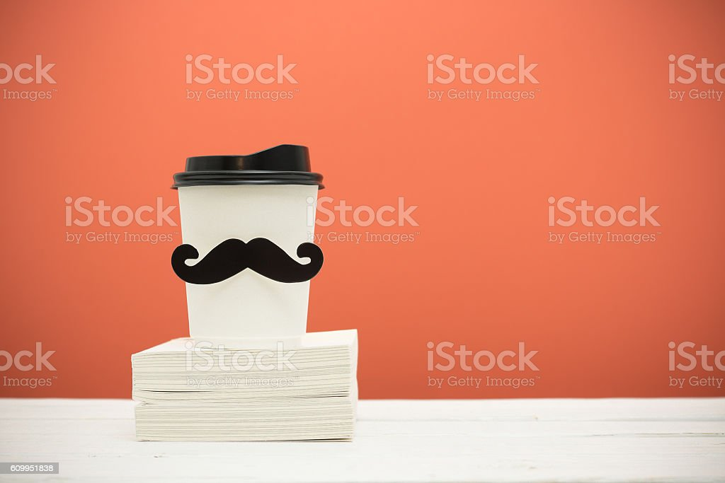 Books and cup with mustache stock photo