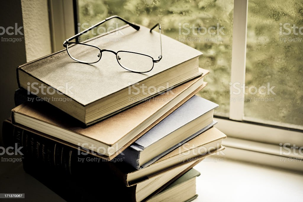 Books and eyeglasses on shelf by window stock photo