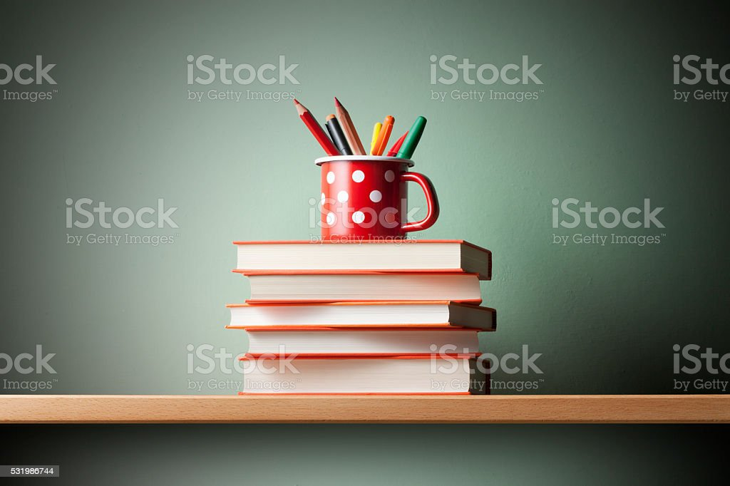 Books and pen holder on the shelf stock photo