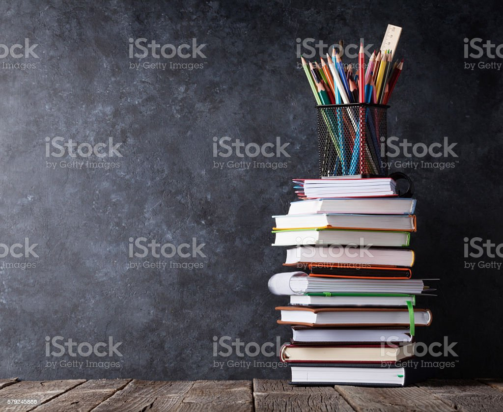 Books and supplies in front of chalk board stock photo