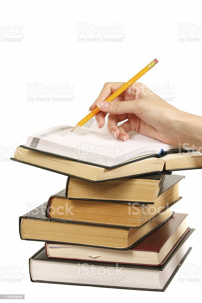 books and woman hand writes in a notebook royalty-free stock photo