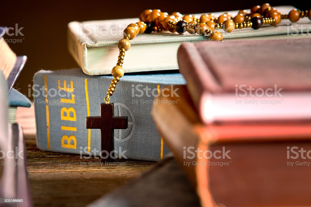 books, bible and rosary in the bookcase stock photo