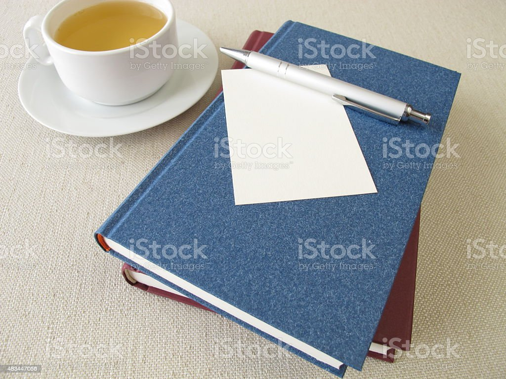 Books, blank sheet of paper and cup of tea stock photo