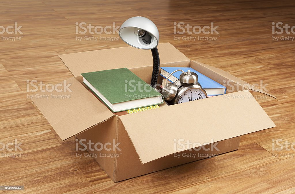 Books, Desk Lamp, and Alarm Clock in Cardboard Box royalty-free stock photo