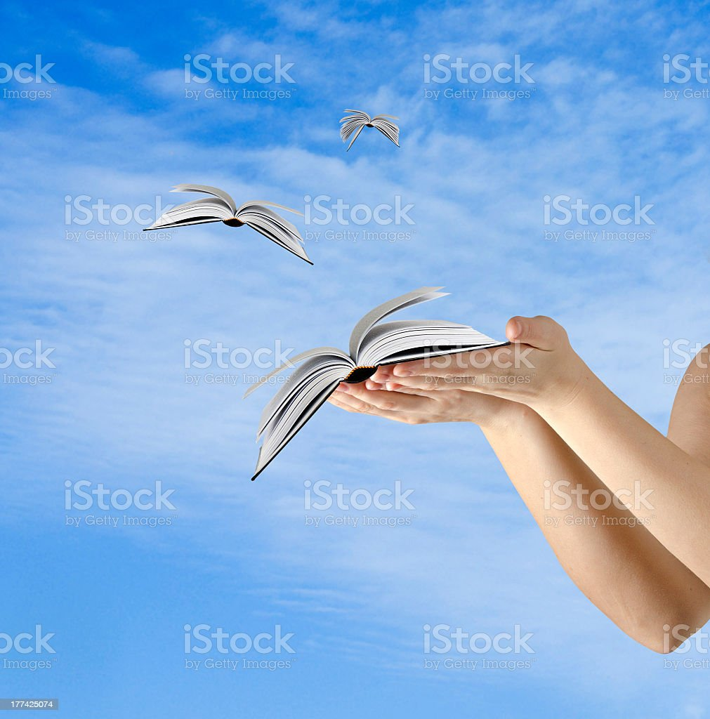 Books flying out of a person's hands into the cloudy sky stock photo