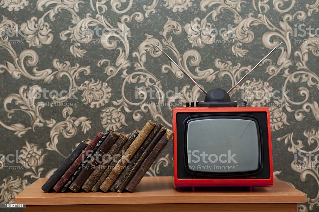 Books leaning on old fashioned tv stock photo