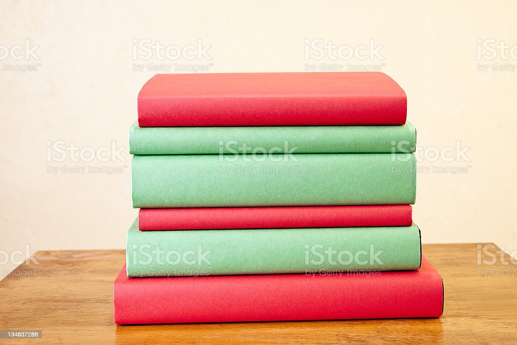 Books of red and green on desk showing spines royalty-free stock photo