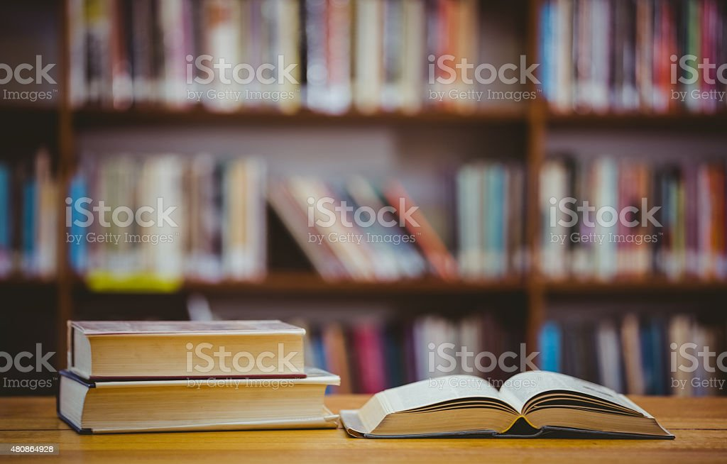 Books on desk in library stock photo