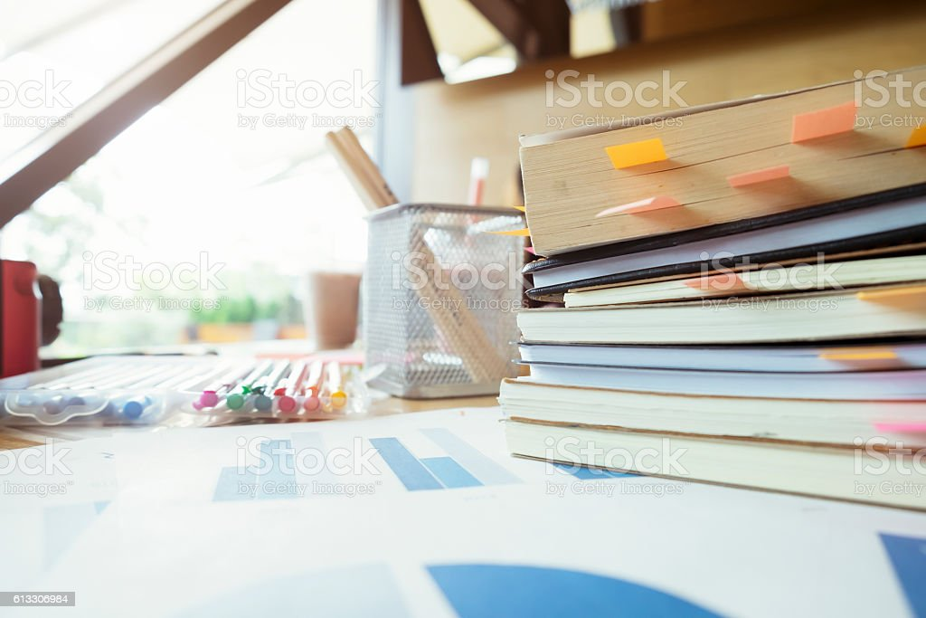 Books with post-it bookmarks on working table. stock photo