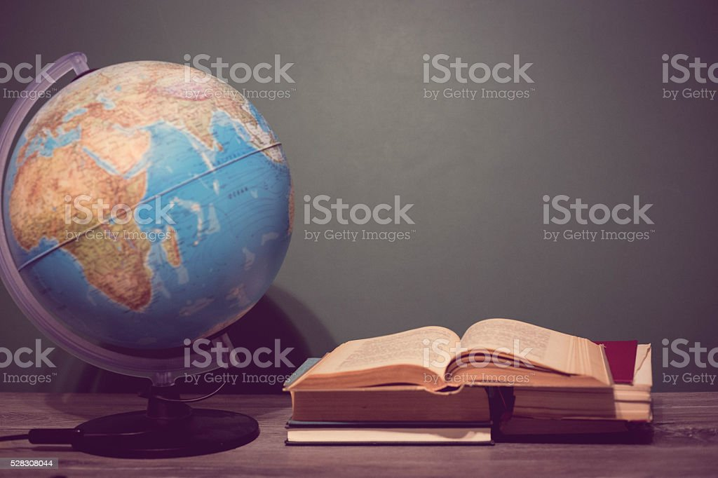 Books with World desktop globe on the table stock photo