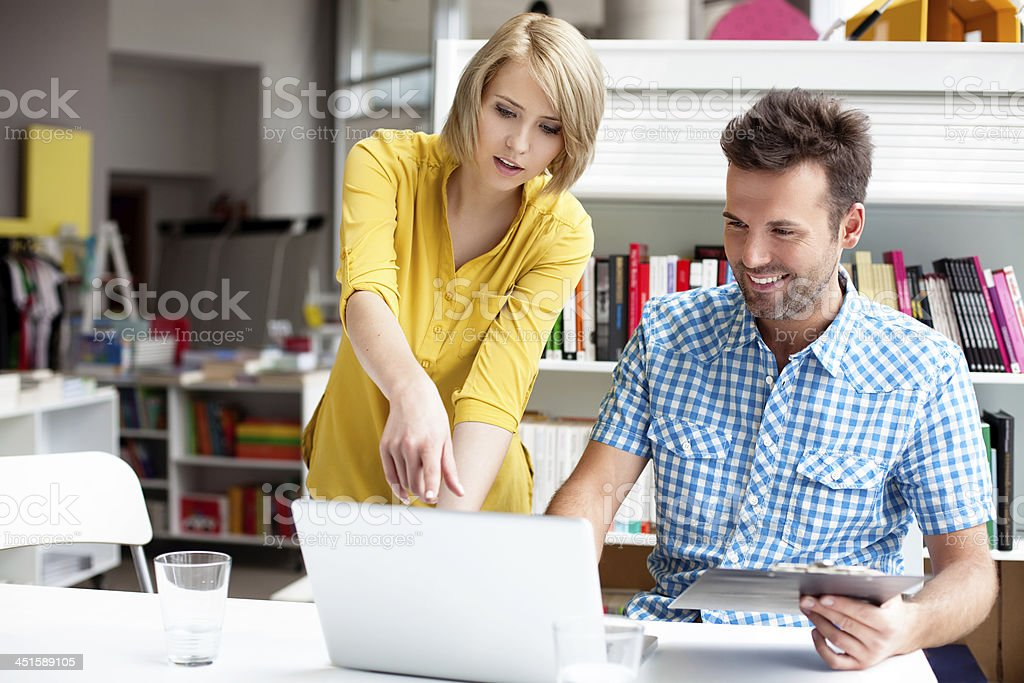 Bookshop managers working on laptop stock photo