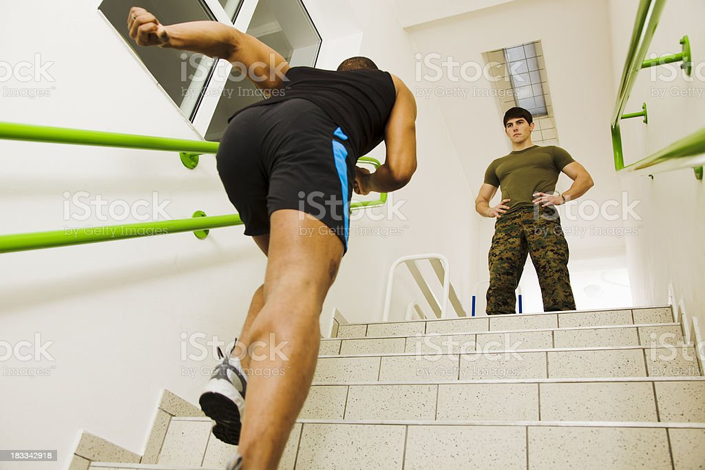 boot camp trainer watches trainee run up stairs royalty-free stock photo