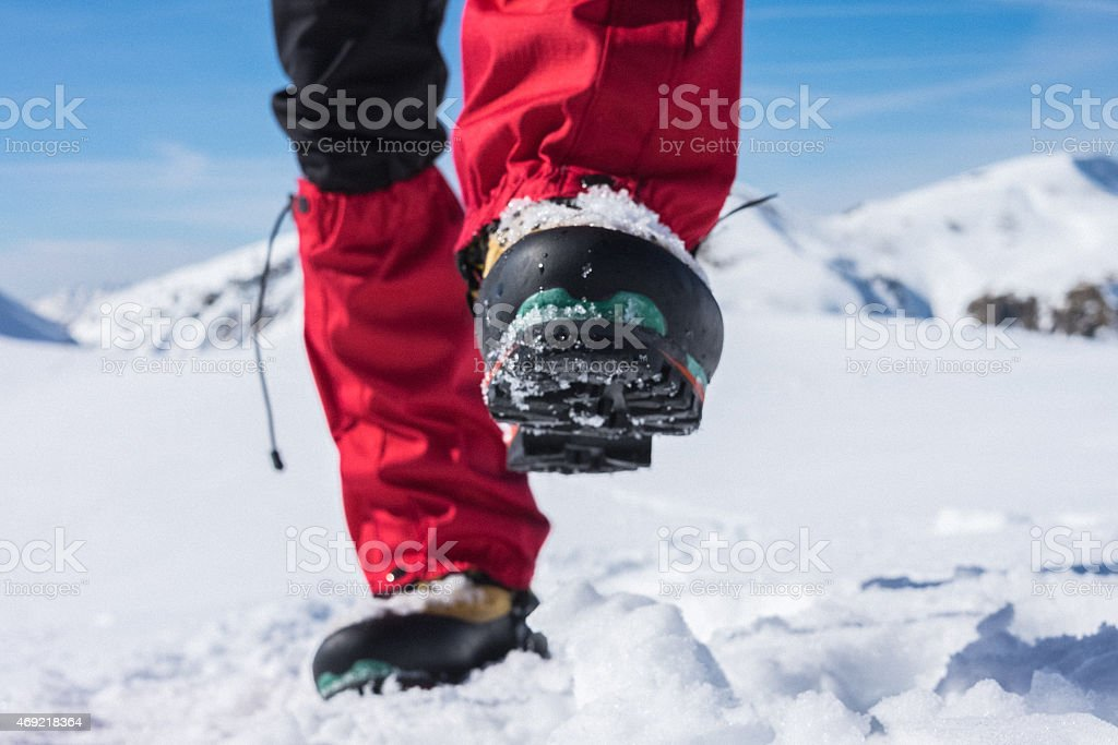 Boot of mountaineer on snowy path stock photo