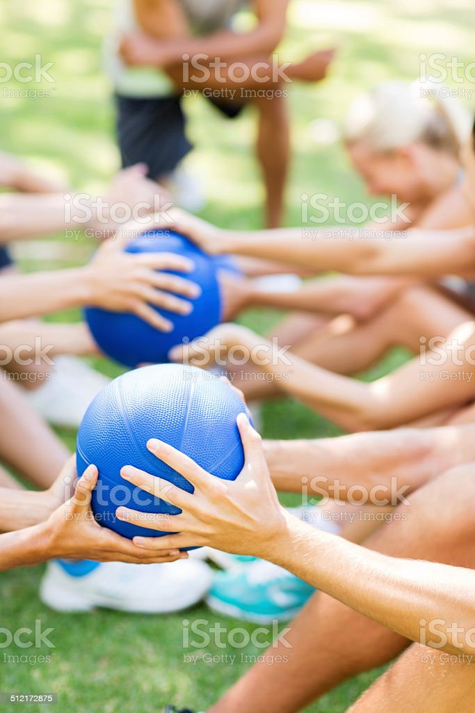 Bootcamp Class Exercising With Medicine Balls In Park stock photo