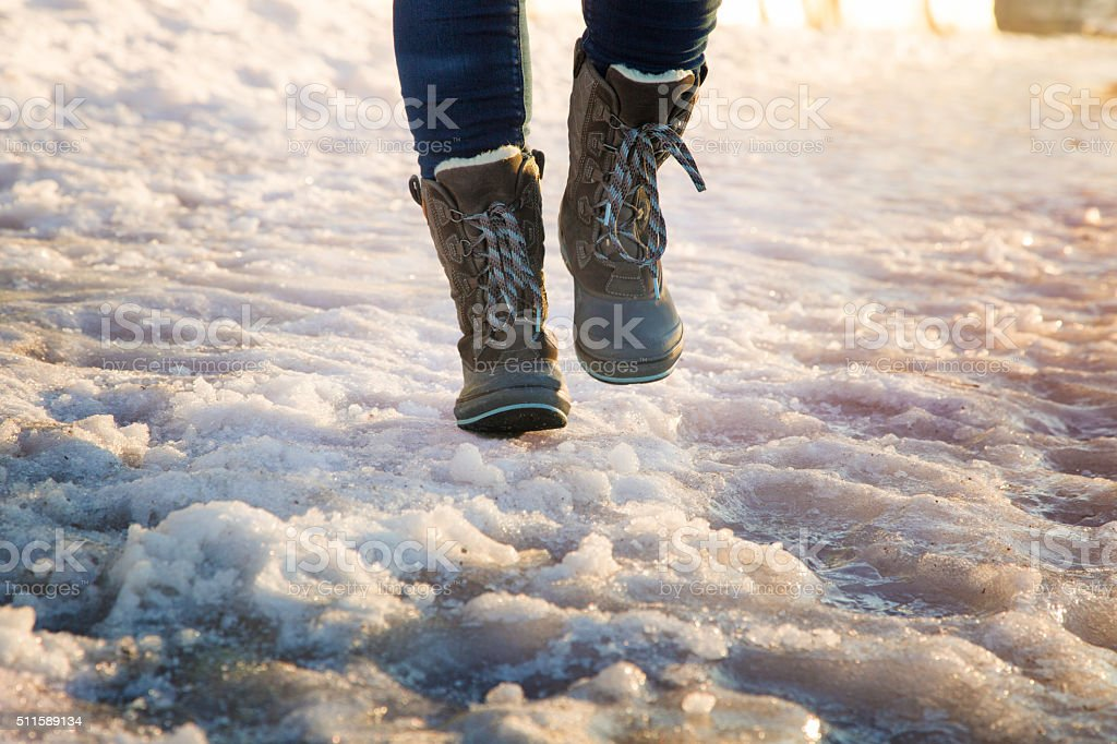 Booted legs running on ice stock photo
