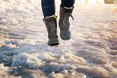 Booted legs running on ice