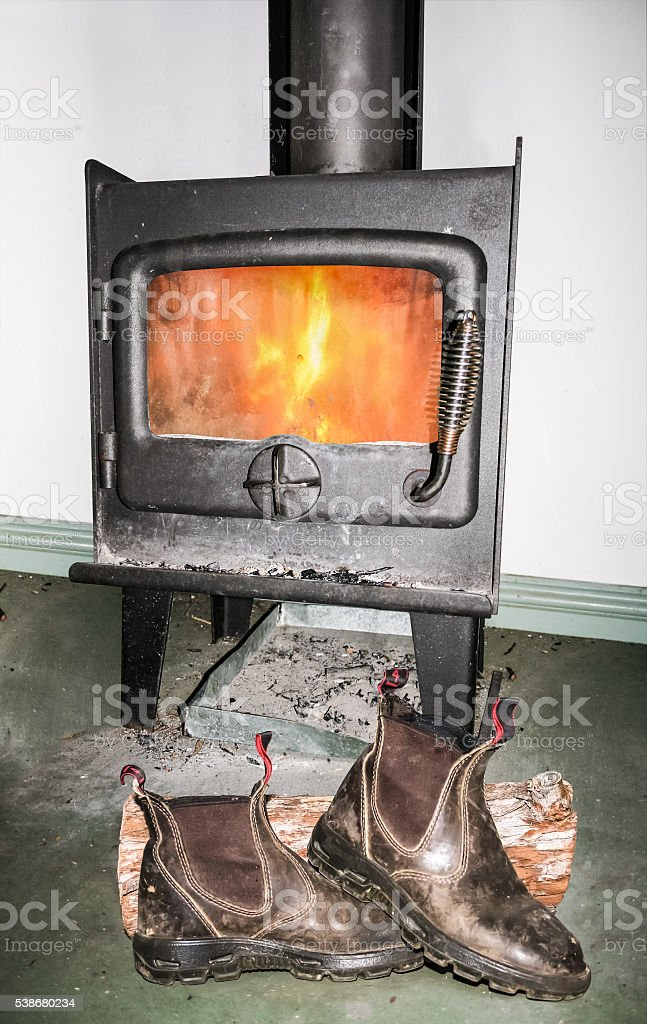 Boots drying in front of fire stock photo