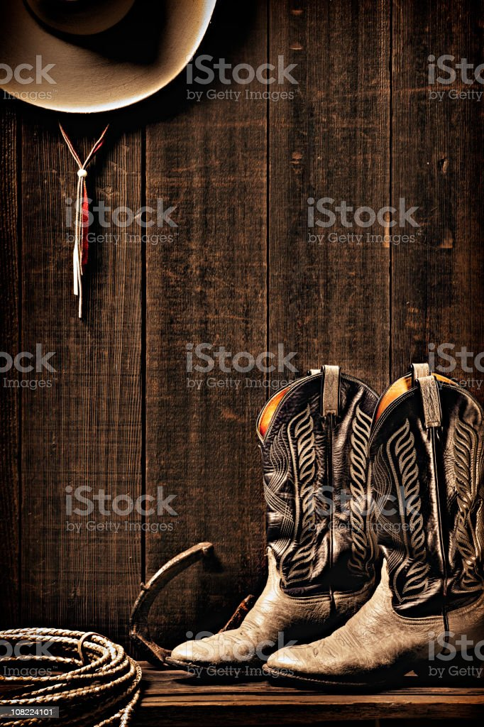 Boots, Lariat and Cowboy Hat Hanging on Wall stock photo