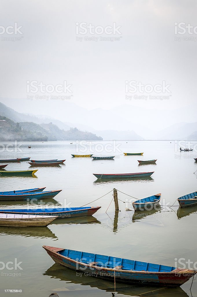 Boots on Fewa lake in Pokhara during misty day royalty-free stock photo