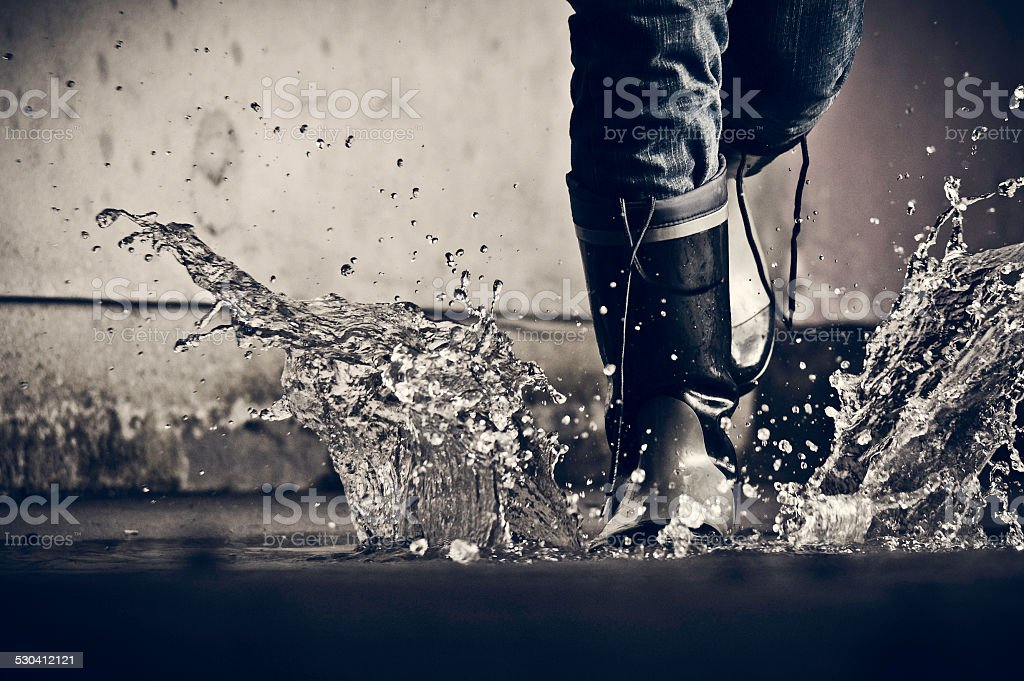 Boots splashing in a puddle stock photo
