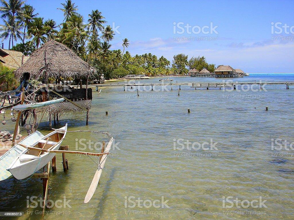 Bora Bora Bungalows and fishing boat on turquoise beach, Polynesia royalty-free stock photo