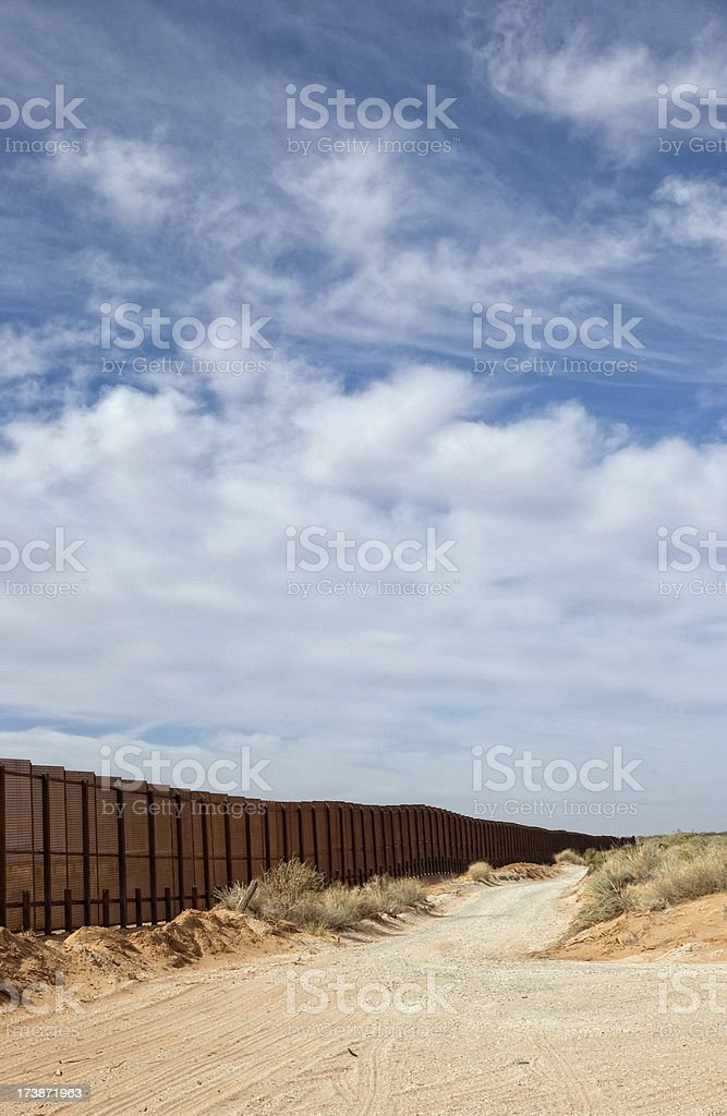Border Fence Along Dirt Road royalty-free stock photo