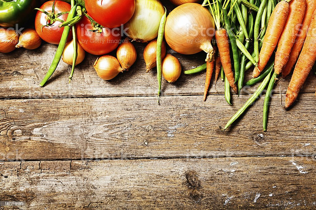 Border of fresh vegetables on weathered wooden background stock photo