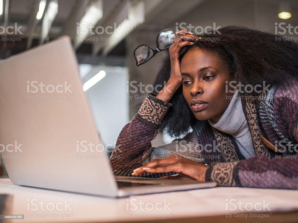 Bored African American woman surfing the Internet. stock photo