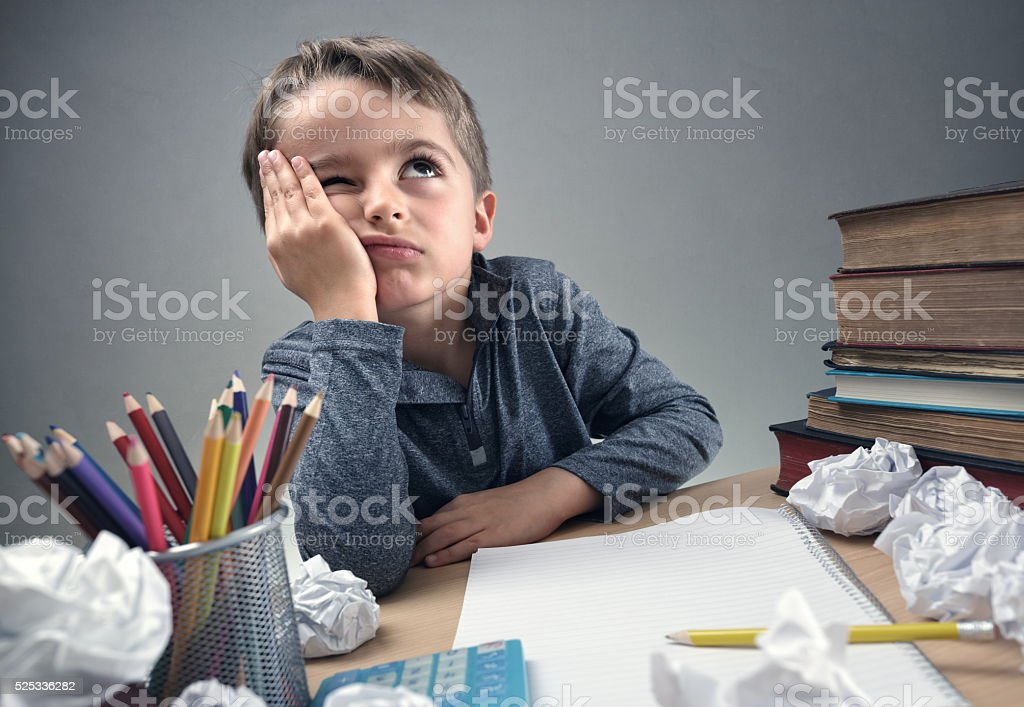 Bored and fed boy up doing his homework stock photo