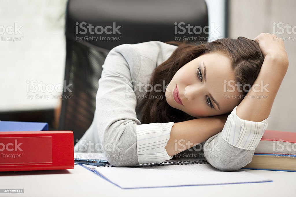 bored and tired young woman lying on table stock photo
