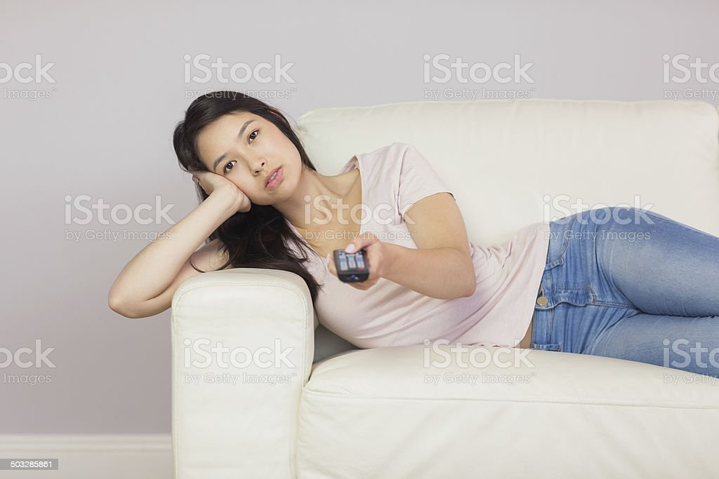 Bored asian girl lying on the couch watching tv stock photo