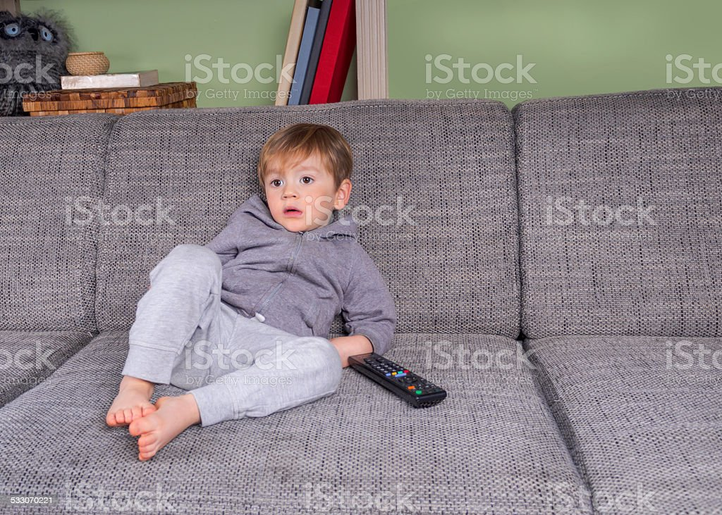 bored boy on the couch watching tv stock photo
