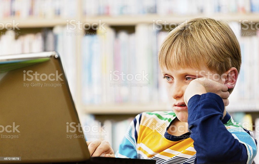 Bored boy sitting at computer in library is not happy! stock photo