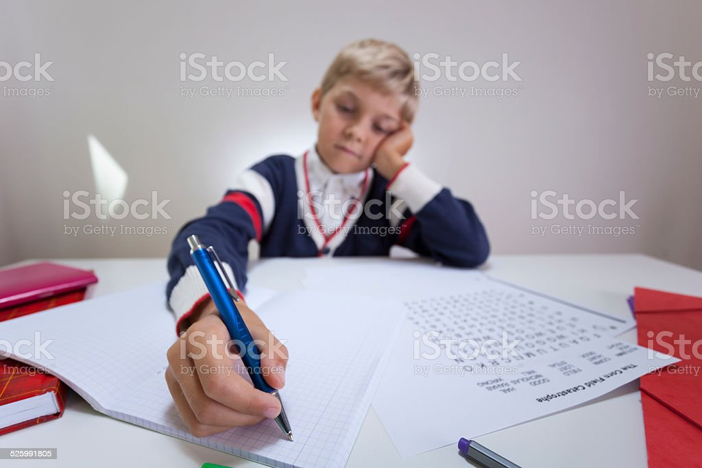 Bored boy writing in notebook stock photo